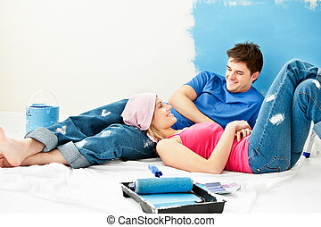 Happy couple relaxing after painting a room in their new...