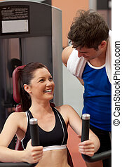 Joyful athletic woman using a shoulder press with her coach...