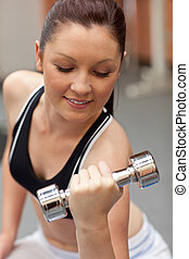 Portrait of a beautiful woman working out with dumbbells in...
