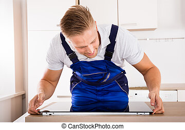 Repairman Installing Induction Cooker - Smiling Male...