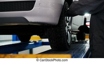 Car mechanic screwing pin car wheel of automobile in garage, slider