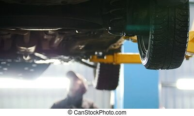 Automobile diagnostic - mechanic working under a lifted car,...