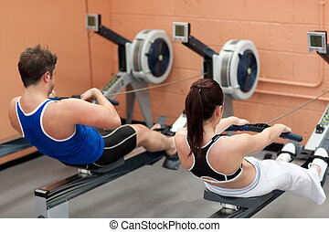 Concentrated people using a rower in a fitness center