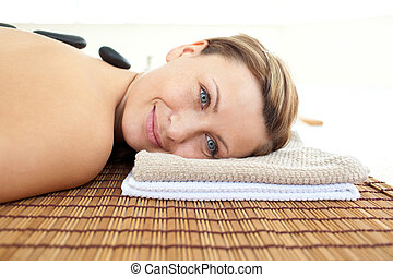 Portrait of a young woman lying on a massage table with hot stones in a health spa