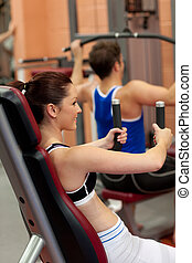 Radiant athletic woman using a shoulder press in a fitness...