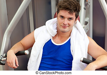 Young man sitting on a bench press