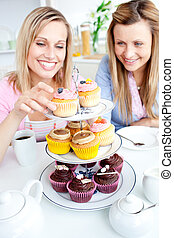 Positive young women eating cakes in the kitchen at home