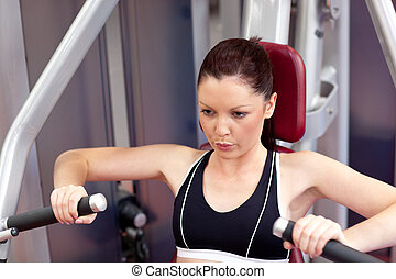 Serious athletic woman using a bench press in a fitness...