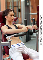 Self-assured athletic woman using a shoulder press in a...