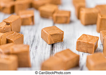 Portion of Caramel pieces on wooden background (selective...