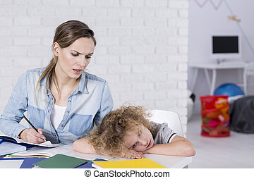 Bored child at desk - Bored child lying with head on desk...