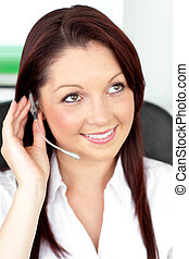 Serious young businesswoman with earpiece in a call center...