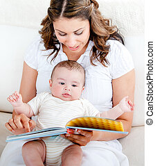 Loving mother reading a story to her adorable baby sitting...