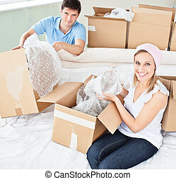 Merry young couple unpacking boxes with glasses in their new...