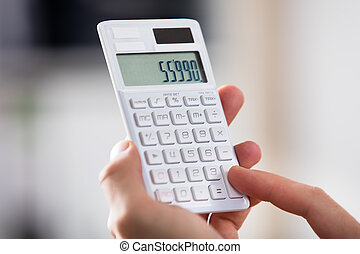 Close-up Of A Person Holding Calculator