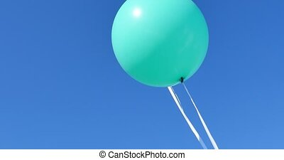two turquoise baloons in the sky.