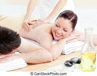 Glowing young couple receiving a back massage in a spa...
