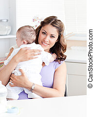 Positive young mother holding her baby in the kitchen at...