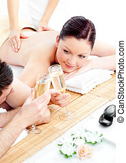 young couple in spa with champagne