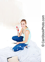 Cheerful young woman painting a room in her new house
