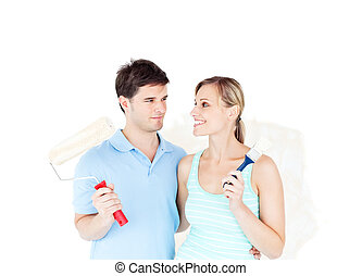 Lovely young couple painting a room