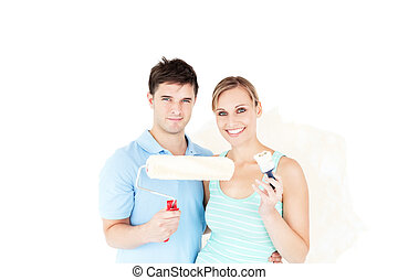 Charming caucasian couple painting a room