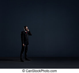 Businessman with a smartphone on black - Businessman with...