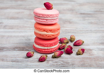 Pink macaroons and rosebuds on wooden table. Valentine's Day...