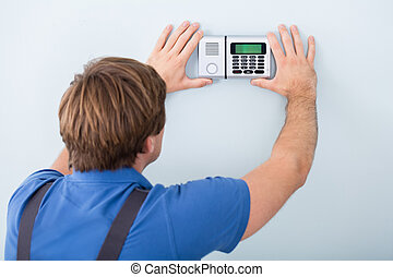 Repairman Installing Security System - Rear View Of...