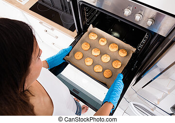 Woman Baking Cookies In Oven