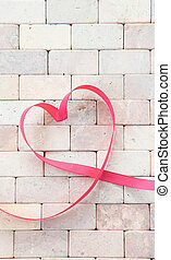 Gift ribbon in a heart shape on rustic stone background