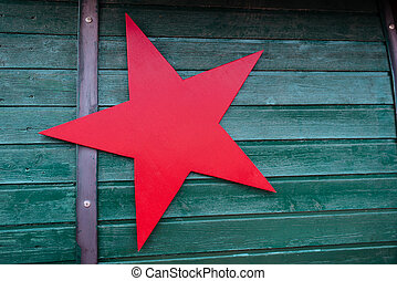 Red star on green wooden background