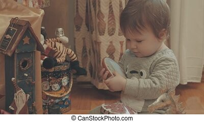 Little baby playing on the floor with christmas toys. Eye...