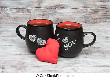 Two black cups with and chalk inscription i love you
