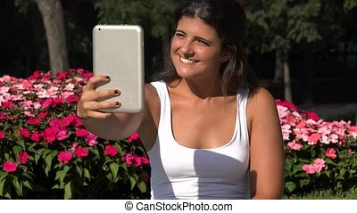 Female Selfie In Park Using Tablet