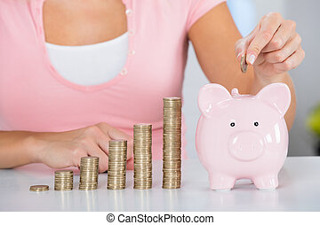 Woman Inserting Coin In The Piggybank - Close-up Of Young...