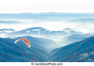 Paragliders launched into air from the very top of a snowy...