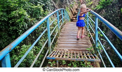 Little Blond Girl Walks along Bridge over Canyon Smiles in...