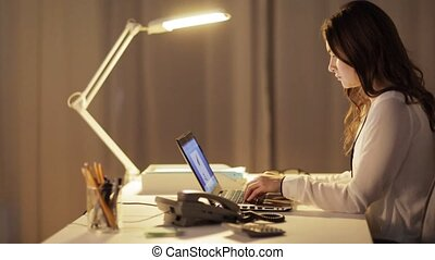 woman with laptop calling on phone at night office -...