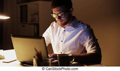man with laptop and papers working at night office -...