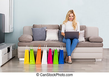 Woman Shopping Online Using Laptop - Woman Sitting On Couch...