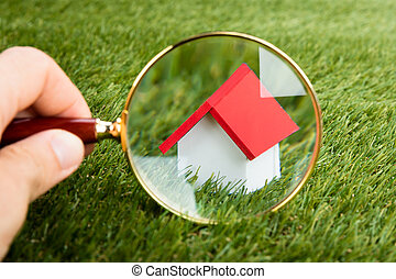 Magnifying Glass Inspecting A Model House - Person Hands...