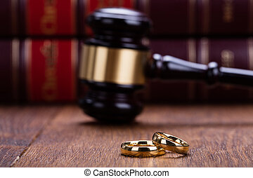 Close-up Of Wedding Rings With Gavel On Wooden Desk In...