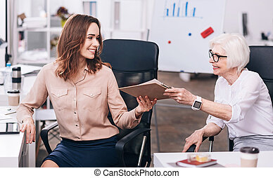 Glad businesswomen sharing papers at the workplace