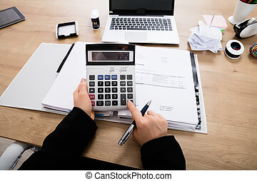 Businesswoman Calculating Invoice - Close-up Of A Accountant...