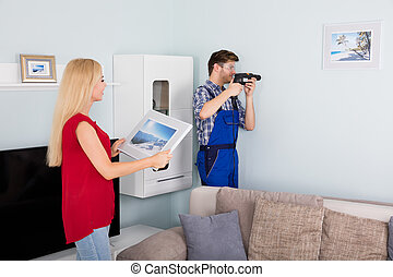 Young Man Using Power Drill On White Wall At Home