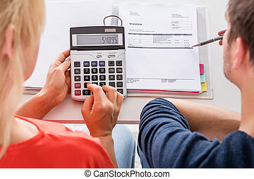 Couple Using Calculator For Calculating Invoice - High Angle...