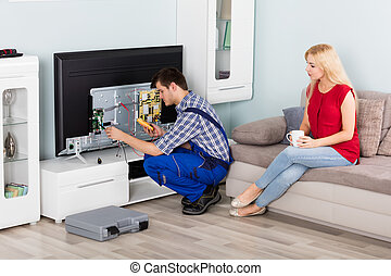 Woman Looking At Technician Repairing Television - Young...