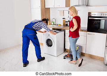 Male Worker Repairing Washer In Kitchen Room - Woman Looking...