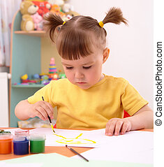 Child draws with paints in preschool
